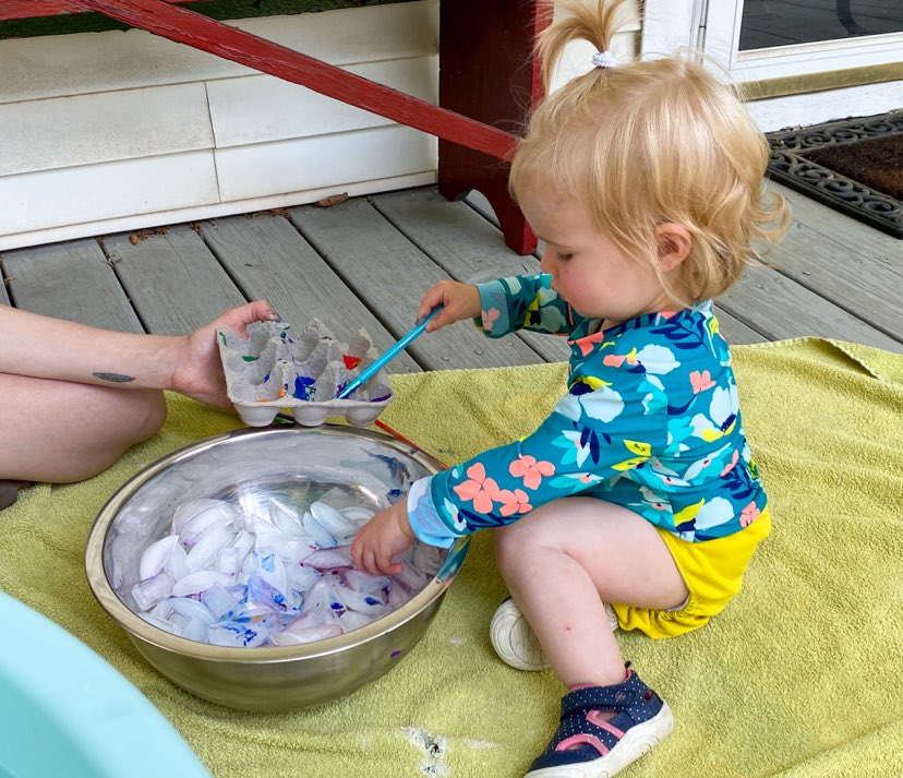 Little girl with paint brush painting icecubes